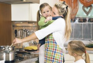 woman holding daughter while cooking in kitchen