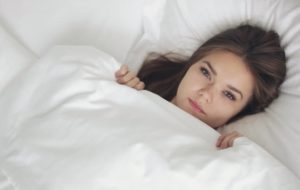 woman with white bed sheets pulled up to her chin